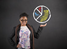 African woman holding hand out with pie chart on blackboard background Stock Photo