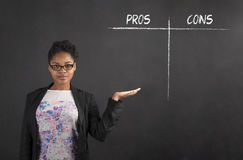 African woman holding hand out showing a pros and cons list on blackboard background Stock Photo