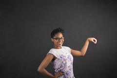 African woman holding object out to side on blackboard background Stock Images