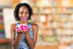 African woman holding rose blossom. Beautiful young african woman holding rose blossom Stock Photos