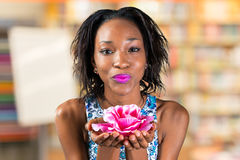 African woman holding rose blossom. Beautiful young african woman holding rose blossom Royalty Free Stock Photos