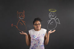 African woman with an I don't know angel and devil gesture on blackboard background. South African or African American black woman teacher or student posing with royalty free stock photo
