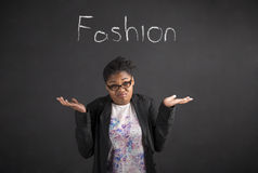 African woman with an I don't know about fashion gesture on blackboard background Stock Photo