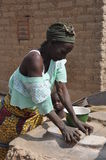African woman knead cereals. A African woman knead some cereals with a stone in order to obtain some flour Stock Photography