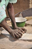African woman knead cereals. A African woman knead some cereals with a stone in order to obtain some flour Royalty Free Stock Images