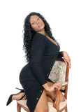 African woman kneeling on chair. Royalty Free Stock Image
