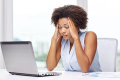 African woman with laptop at office Stock Photos