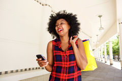 African woman laughing with mobile phone with shopping bags Stock Photography