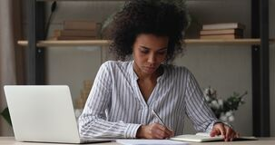 African woman learn paperwork with graphs writes notes in sketchpad