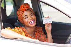 African woman license. Cheerful african woman showing a driving license she just got Royalty Free Stock Images