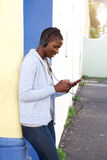 African woman listening to music outside with headphones. Side portrait of african woman listening to music outside with headphones Royalty Free Stock Images