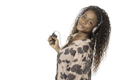 African woman listening to music from phone. African woman standing listening to music from phone with big earphones royalty free stock image