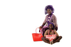 African woman and little girl on the floor in traditional clothing with tote bags. Isolated Royalty Free Stock Image