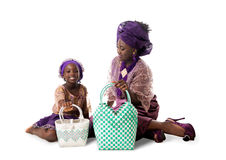 African woman and little girl in traditional clothing with tote bags.Isolated Stock Photos
