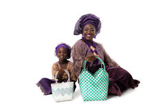 African woman and little girl in traditional clothing with tote bags.Isolated. Beautiful African women and little girl in traditional purple clothing with wicker Royalty Free Stock Photo