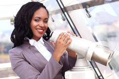 African woman looking through binoculars. Over the city Stock Image