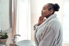 African woman looking at her complexion in a bathroom mirror. Smiling young African woman wearing a robe standing in her bathroom in the morning looking at her stock image