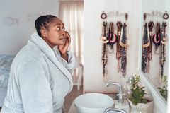 African woman looking at her face in a bathroom mirror. Young African woman wearing a robe standing in her bathroom in the morning looking at her complexion in Royalty Free Stock Photos