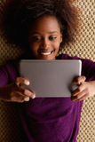 African woman lying down with digital tablet Royalty Free Stock Photos