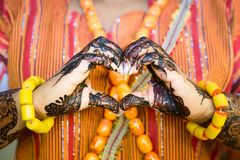African Woman making a Heart Shape with Henna Painted Hands. And Yellow Bracelets royalty free stock photos