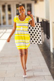 African woman mall. Happy african woman with shopping bag in mall Royalty Free Stock Photography