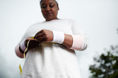 African woman measuring her waist after sports training royalty free stock image