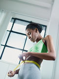 African woman measuring waist with yellow tape Royalty Free Stock Photo