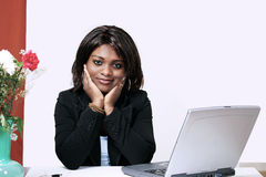 African woman at office desk. Pretty african woman at office desk with laptop Stock Photo