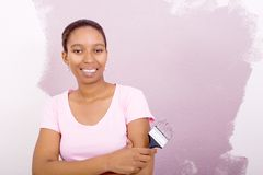 African woman painting wall. A smiling african woman painting the wall in casual clothes Royalty Free Stock Images