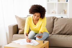African woman with papers and calculator at home Stock Photography
