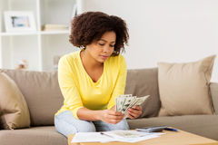 African woman with papers and calculator at home. Budget, finances and people concept - african american woman with papers and calculator counting money at home royalty free stock photo