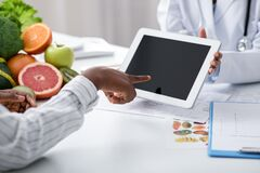 African woman patient touching empty tablet screen