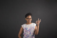 African woman with perfect hand signal on blackboard background Stock Image