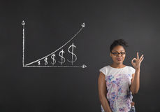 African woman with perfect hand signal with a growing money graph on blackboard background Stock Photos