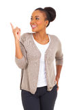 African woman pointing up. Cheerful african woman pointing up isolated on white background Royalty Free Stock Photo