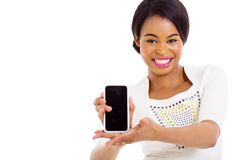 African woman presenting smart phone. Young african american woman presenting smart phone over white background Royalty Free Stock Photo