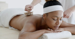 African Woman Receiving Back Massage. Closeup of happy african woman receiving back massage at salon spa Stock Image