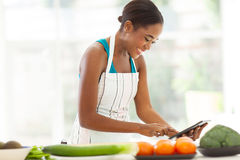 African woman recipe. Pretty african woman searching for a recipe on internet using tablet computer Royalty Free Stock Photo