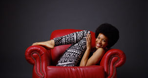 African woman in red leather arm chair kicking legs playfully Stock Image