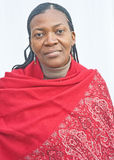 African woman in red patterned shawl. An image of a South African, a nurse, wearing a red patterned shawl for warmth and with delicately plaited hair Royalty Free Stock Images