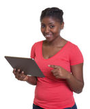 African woman in red shirt working with tablet Royalty Free Stock Images