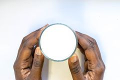 African Woman`s Hand holding glass of warm fresh milk on white background. Top view food and drink for healthy nutrition concept. Good calcium nutrition drink stock image