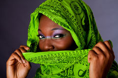 African woman with scarf. The face of an innocent beautiful young African-American woman covering her mouth with green headwrap and purple-green makeup, isolated Royalty Free Stock Photo