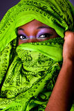 African woman with scarf. The face of an innocent beautiful young African-American woman covering her mouth showing only her eyes with green headwrap and purple Royalty Free Stock Photography