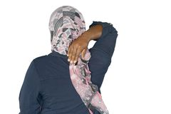 Severe pain in the shoulder of a woman. African woman in scarf with pain in her back isolated on a white background royalty free stock images