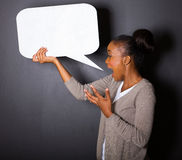 African woman screaming. In blank speech bubble  on black background Royalty Free Stock Images