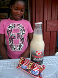 African Woman Sells Obama Biscuits. An African woman sells a package of Obama biscuits, along with a bottle of soymilk, from a roadside stand in Accra, Ghana Royalty Free Stock Photos