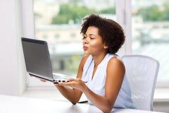 African woman sending kiss to laptop computer Stock Photo