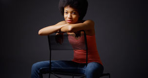 African woman sitting casually with arms over back of chair Stock Photography