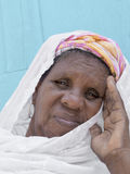 African woman sitting in front of her house Stock Image